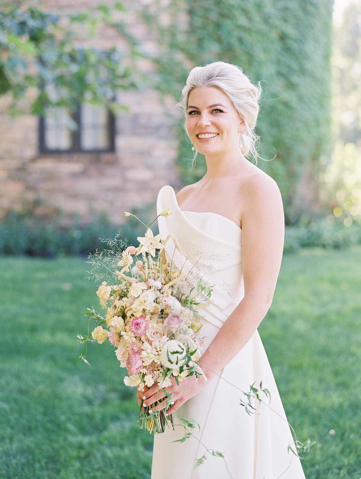 bride smiling holding various white floral wedding bouquet
