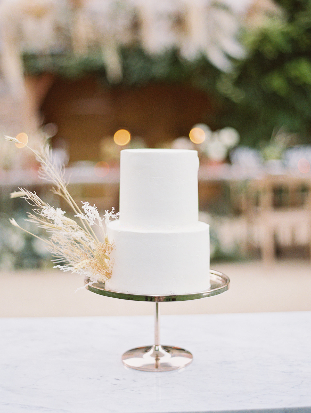 two tier white frosted wedding cake with boho foliage