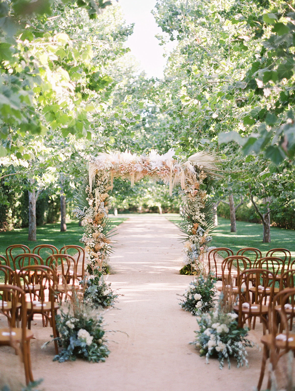floral arch wooden chairs outdoor ceremony setup