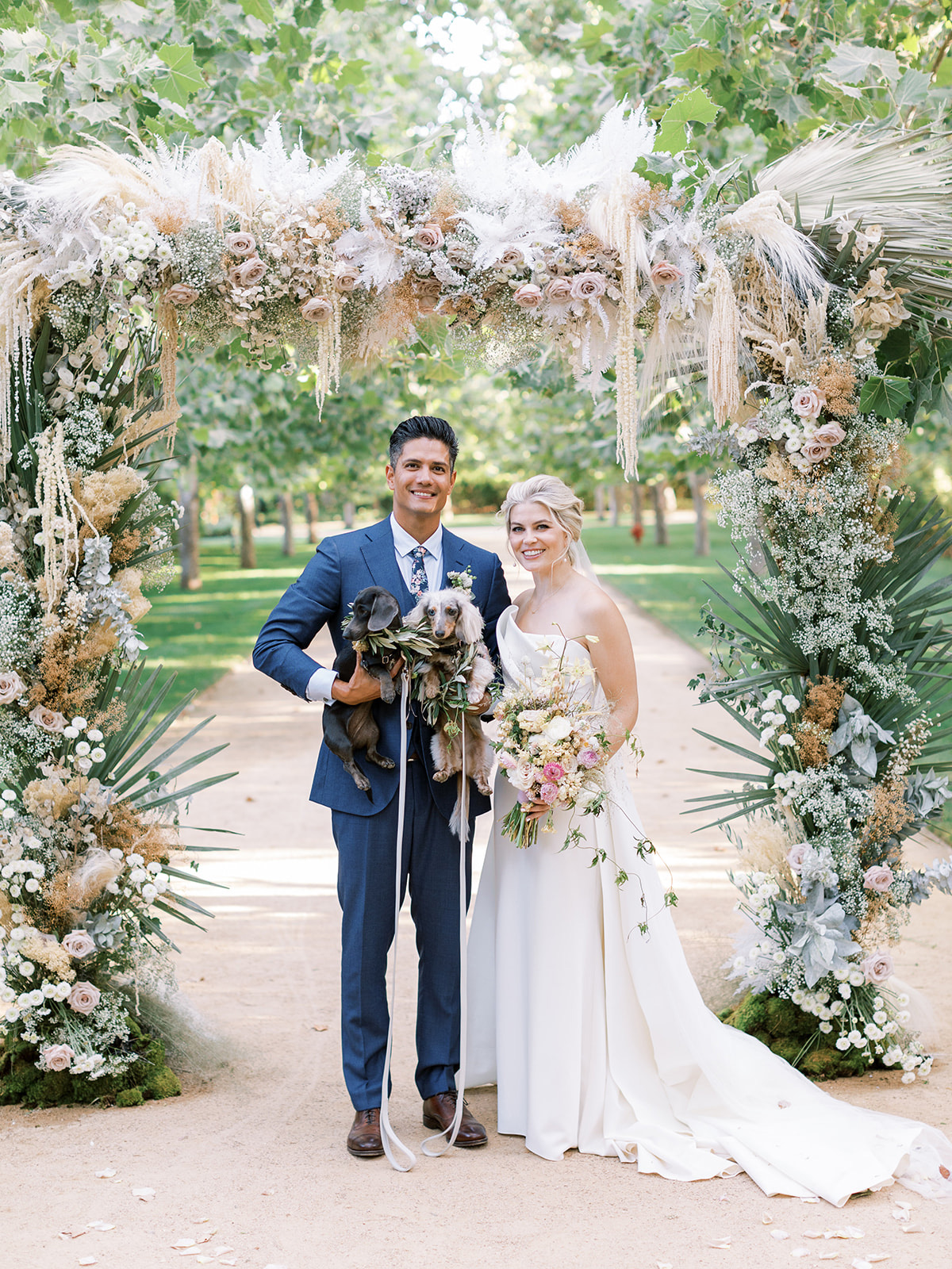 bride and groom with their two dogs standing under floral arch