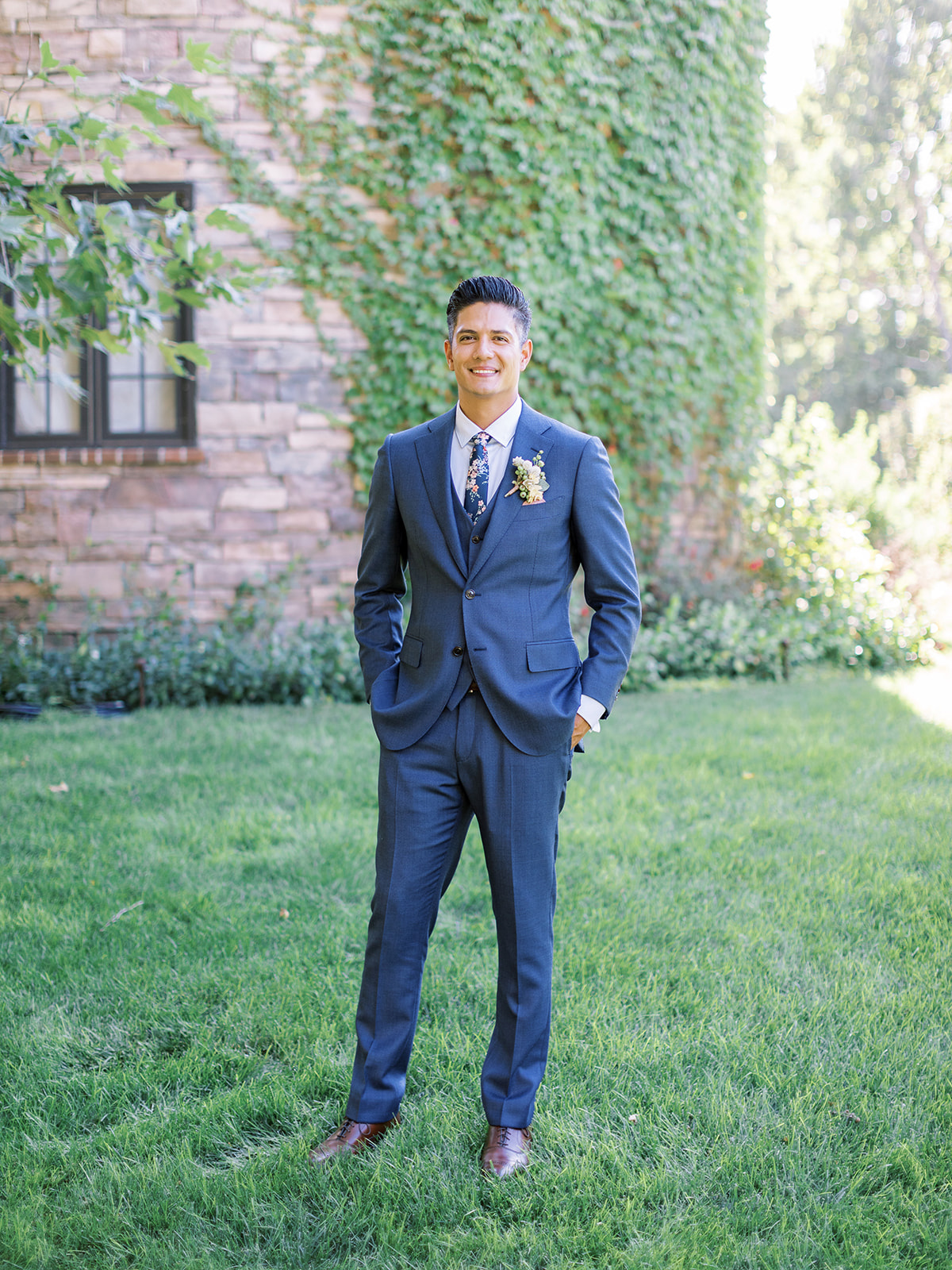 groom smiling wearing a custom three piece navy suit