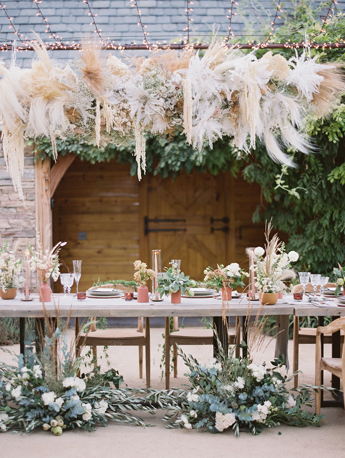 head reception table with rustic greenery and foliage decor