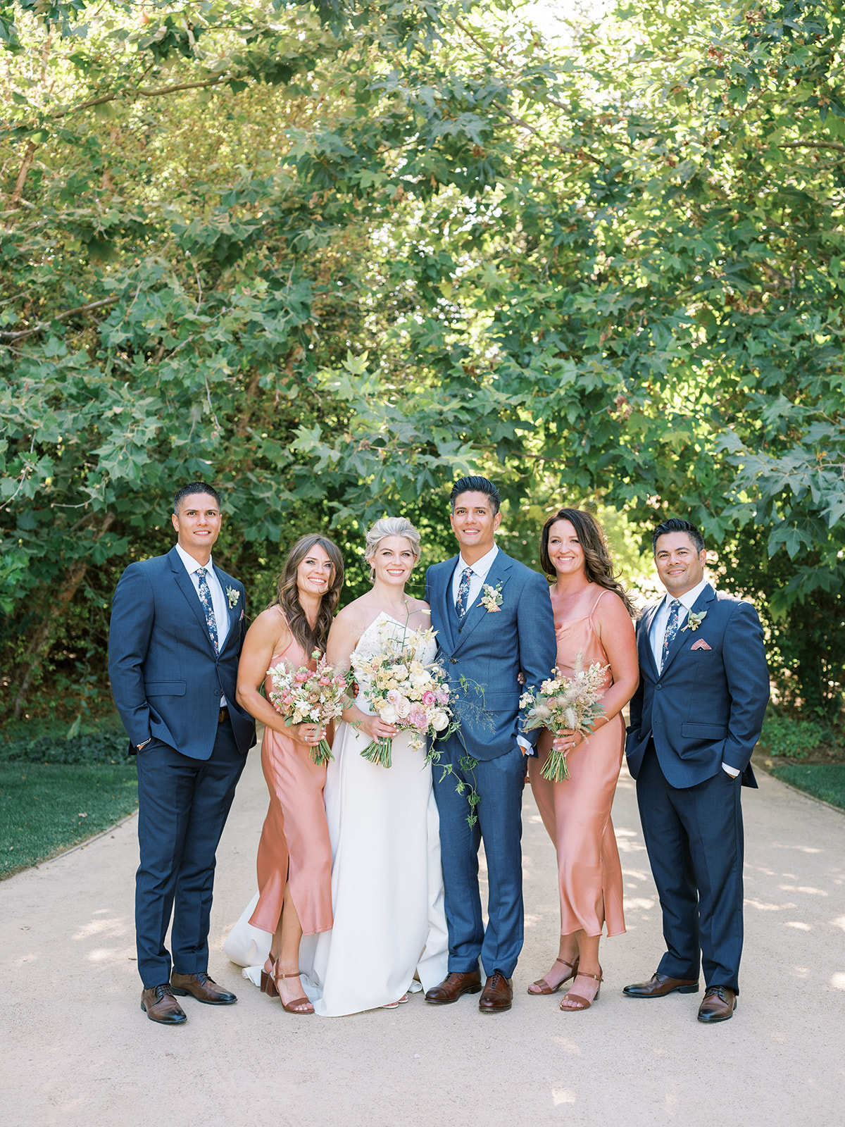 bride and groom standing with wedding party on outdoor pathway