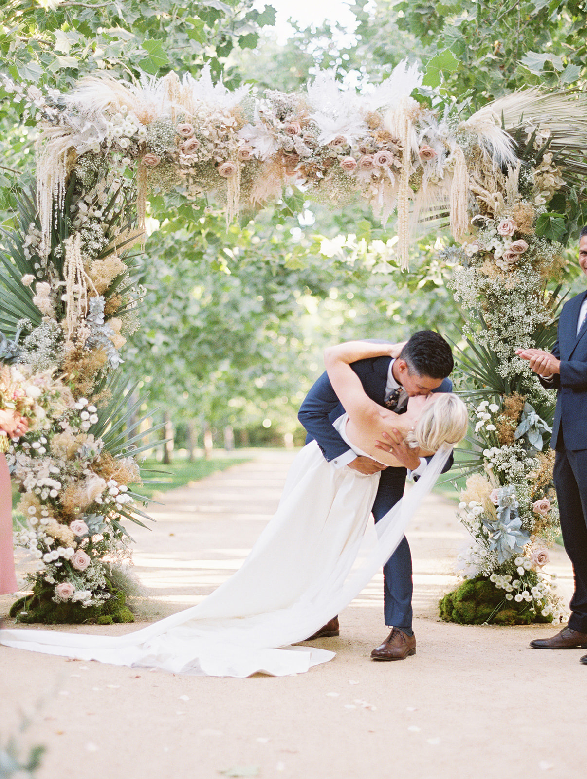 groom dips bride for a kiss under floral arch