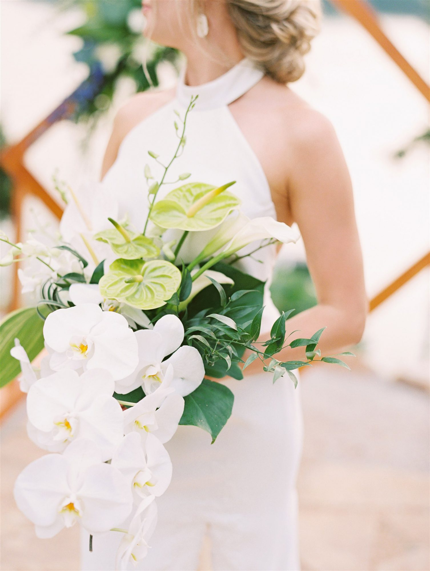 bridal bouquet comprised of white orchids green and white anthurium and white lilies
