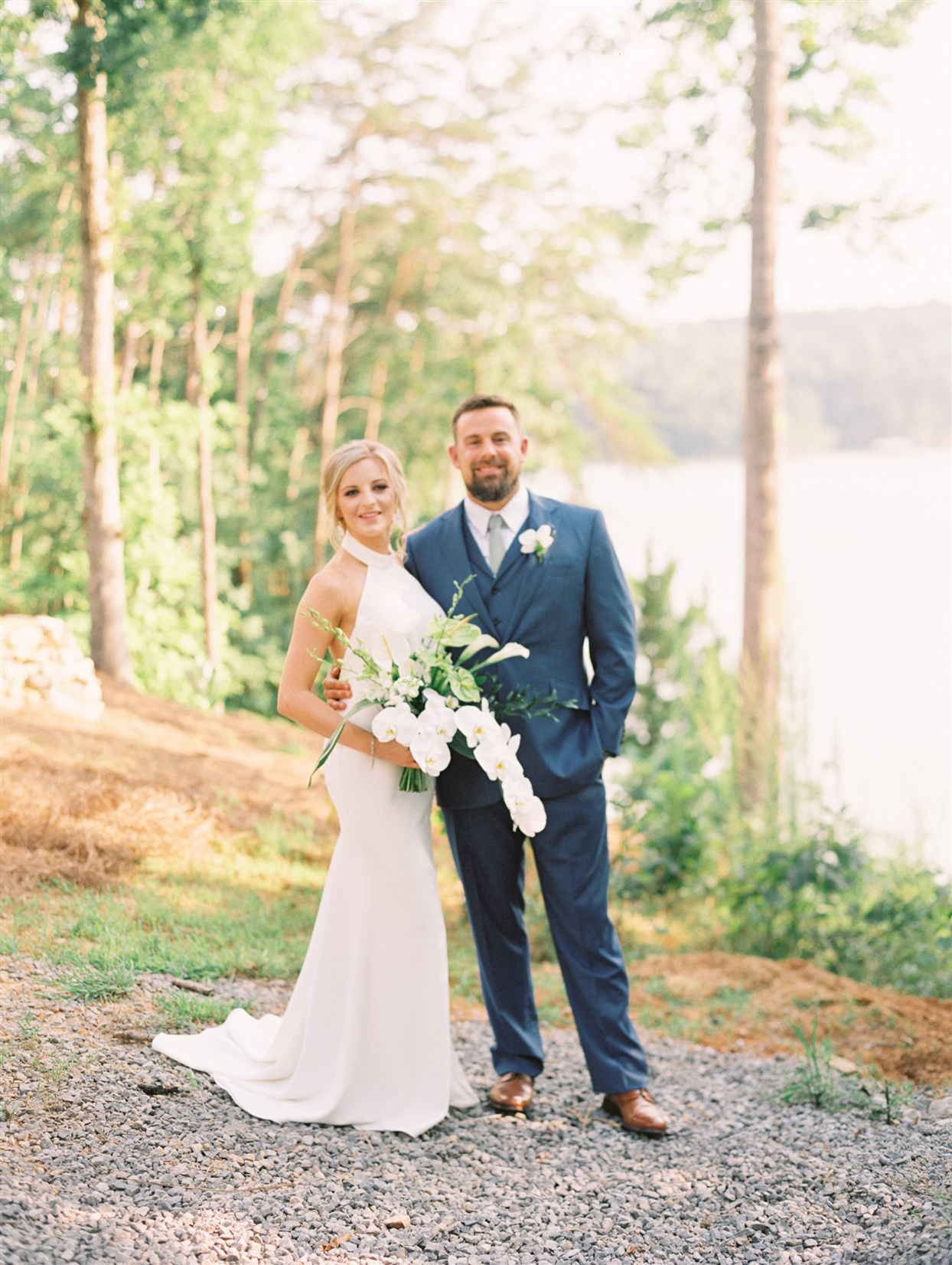 bride and groom posing in front of trees and waterfront
