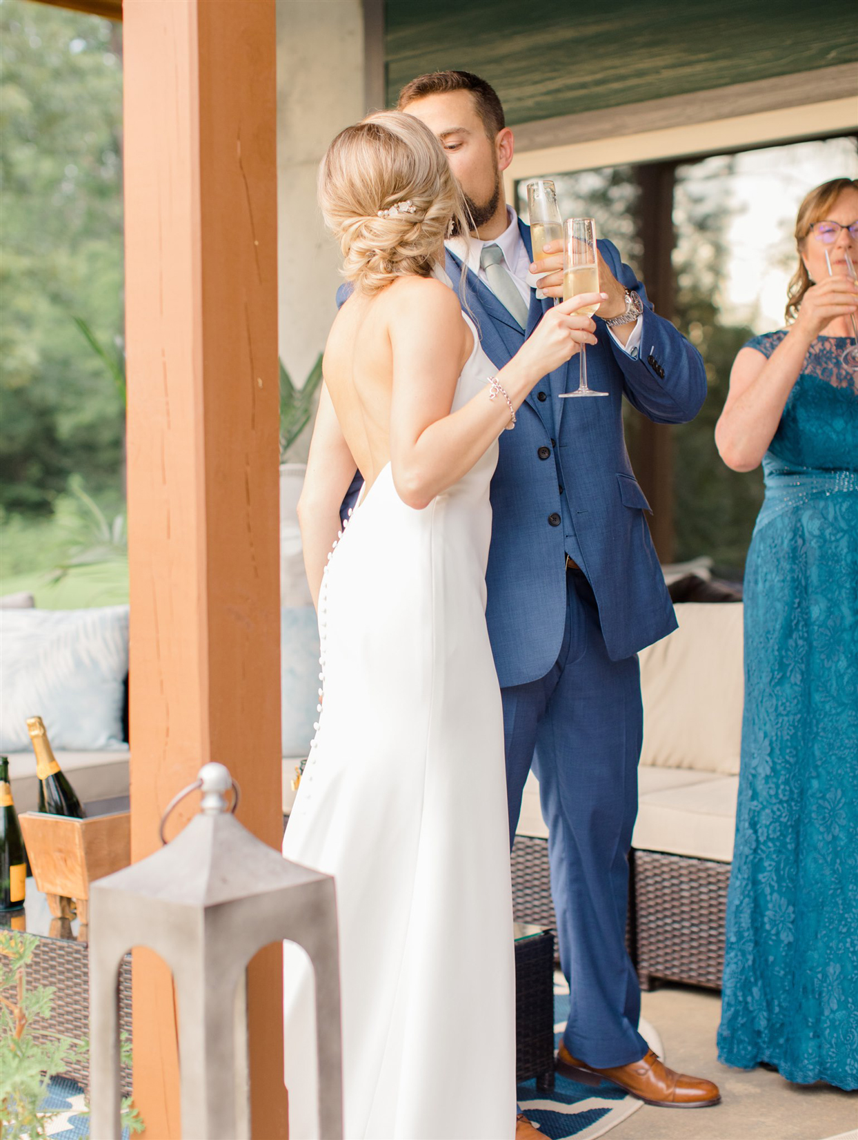 bride and groom cheersing and kissing on porch
