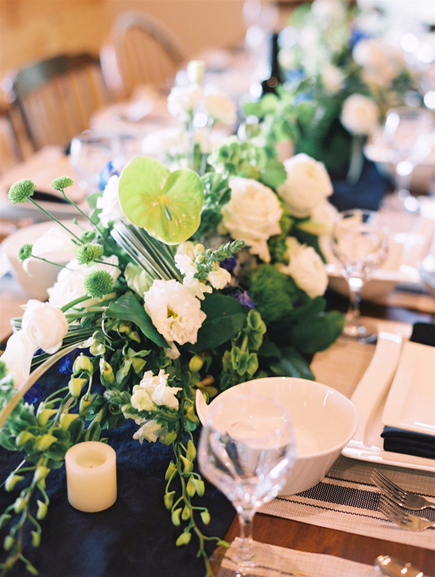 chain of flower arrangements in greens and blues lining center of reception table