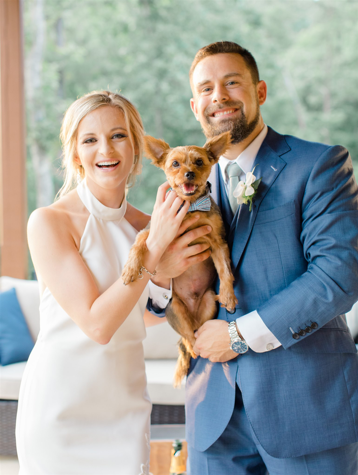 bride and groom holding puppy wearing bowtie