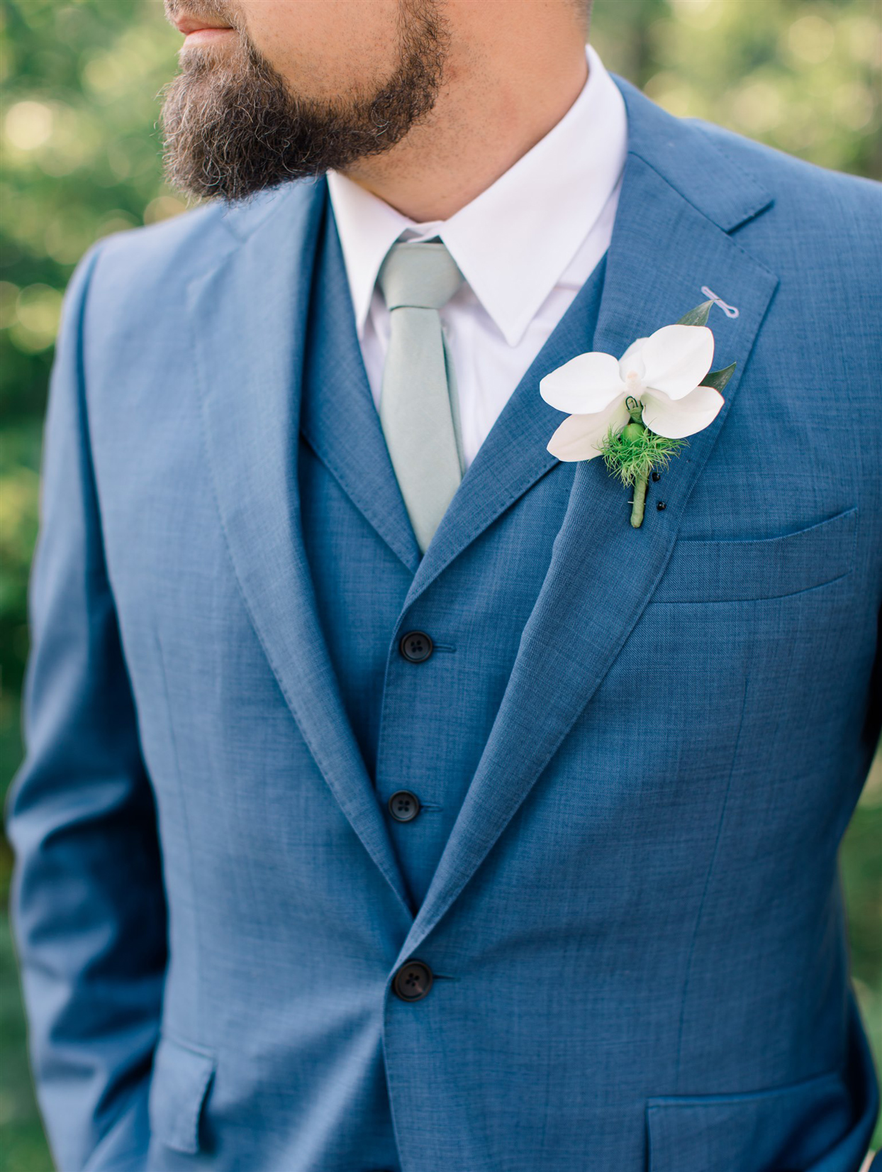 groom wearing blue suit and white orchid boutonniere