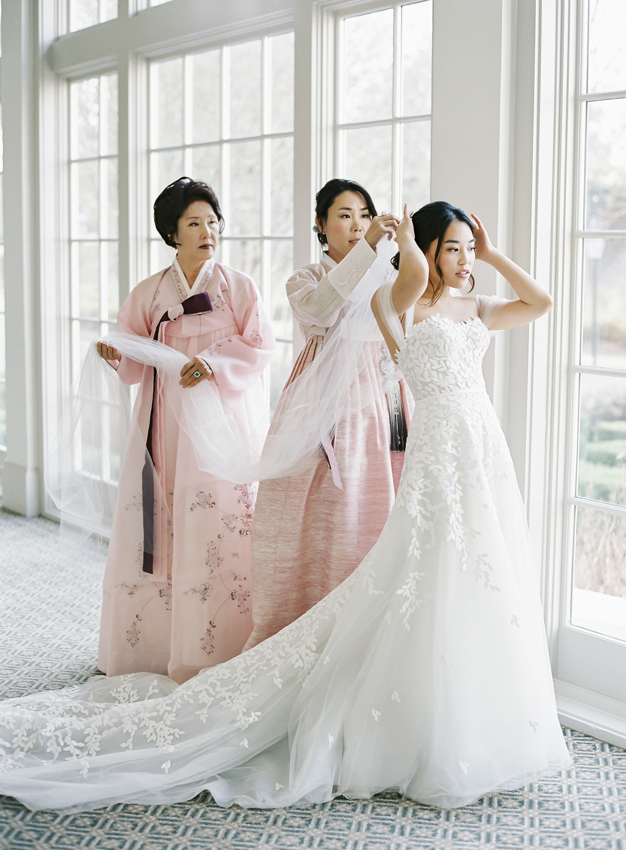 bride getting ready for wedding with women putting on veil