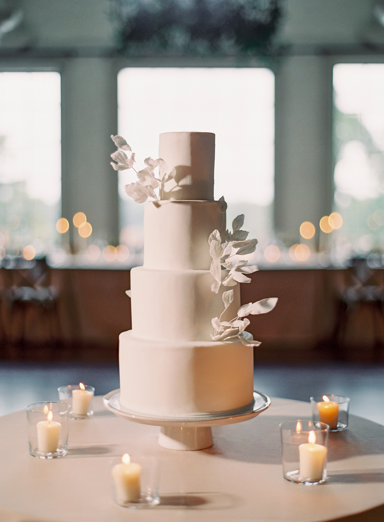 four tier elegant wedding cake surrounded by candles