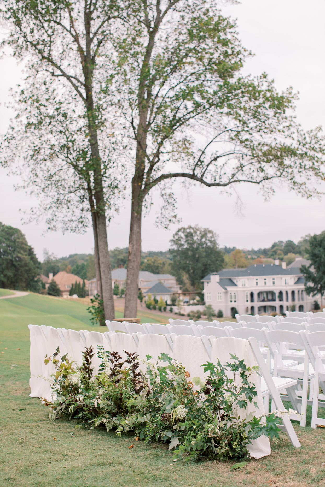 white wedding ceremony chairs set up on lawn overlooking houses