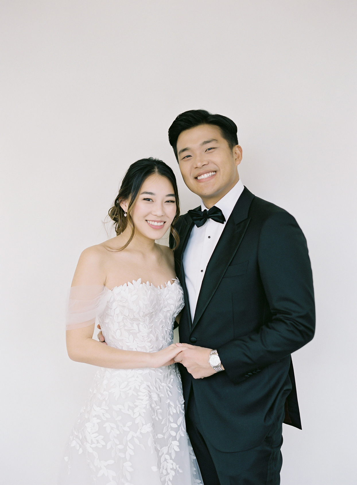 wedding couple portrait against white wall