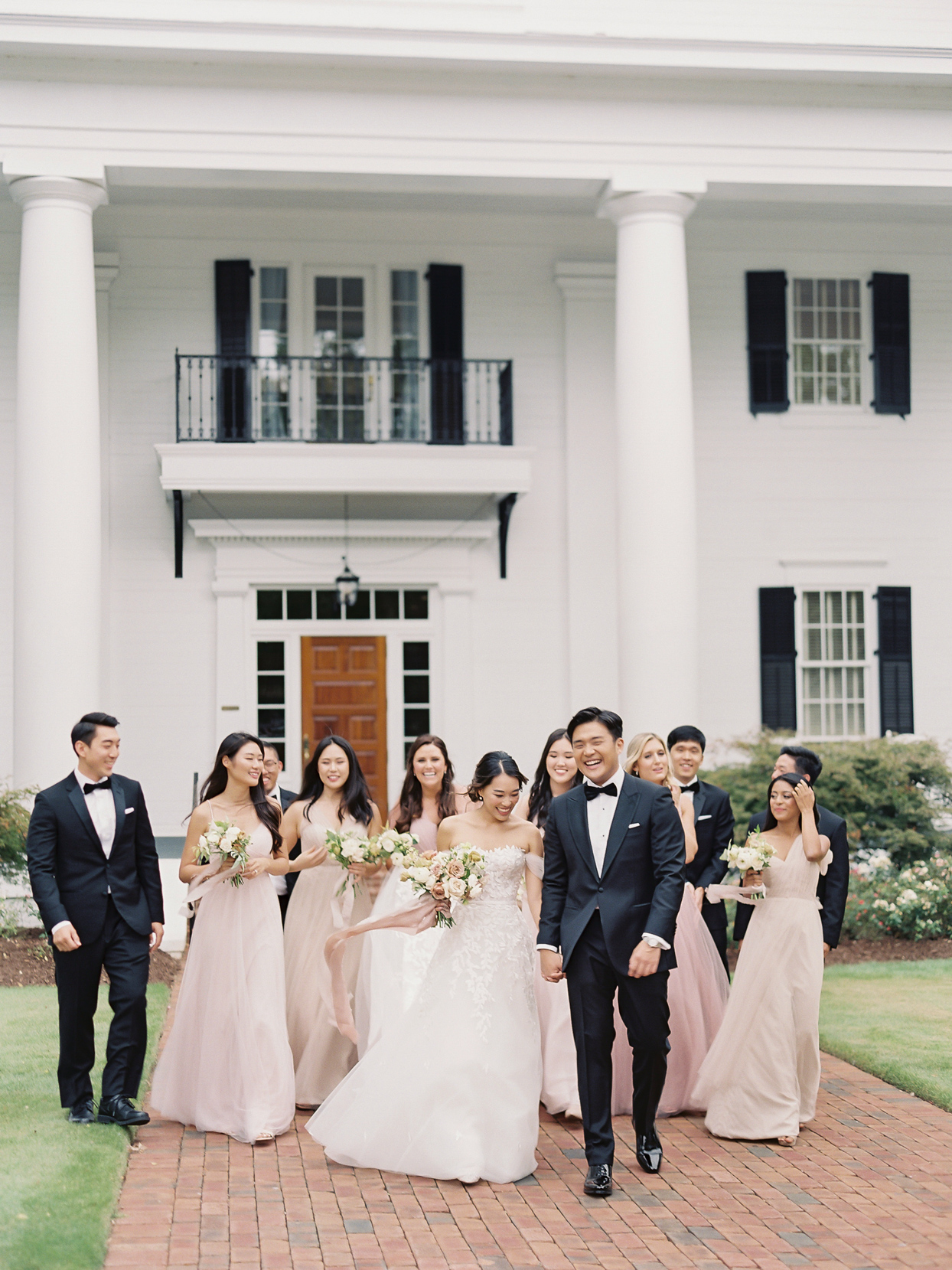 bridal party in blush and black walking in front of house