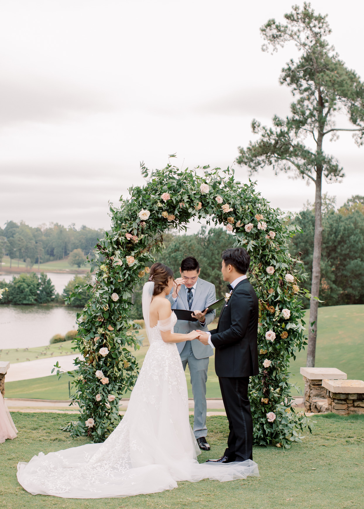 couple exchanging vows in front of floral arch