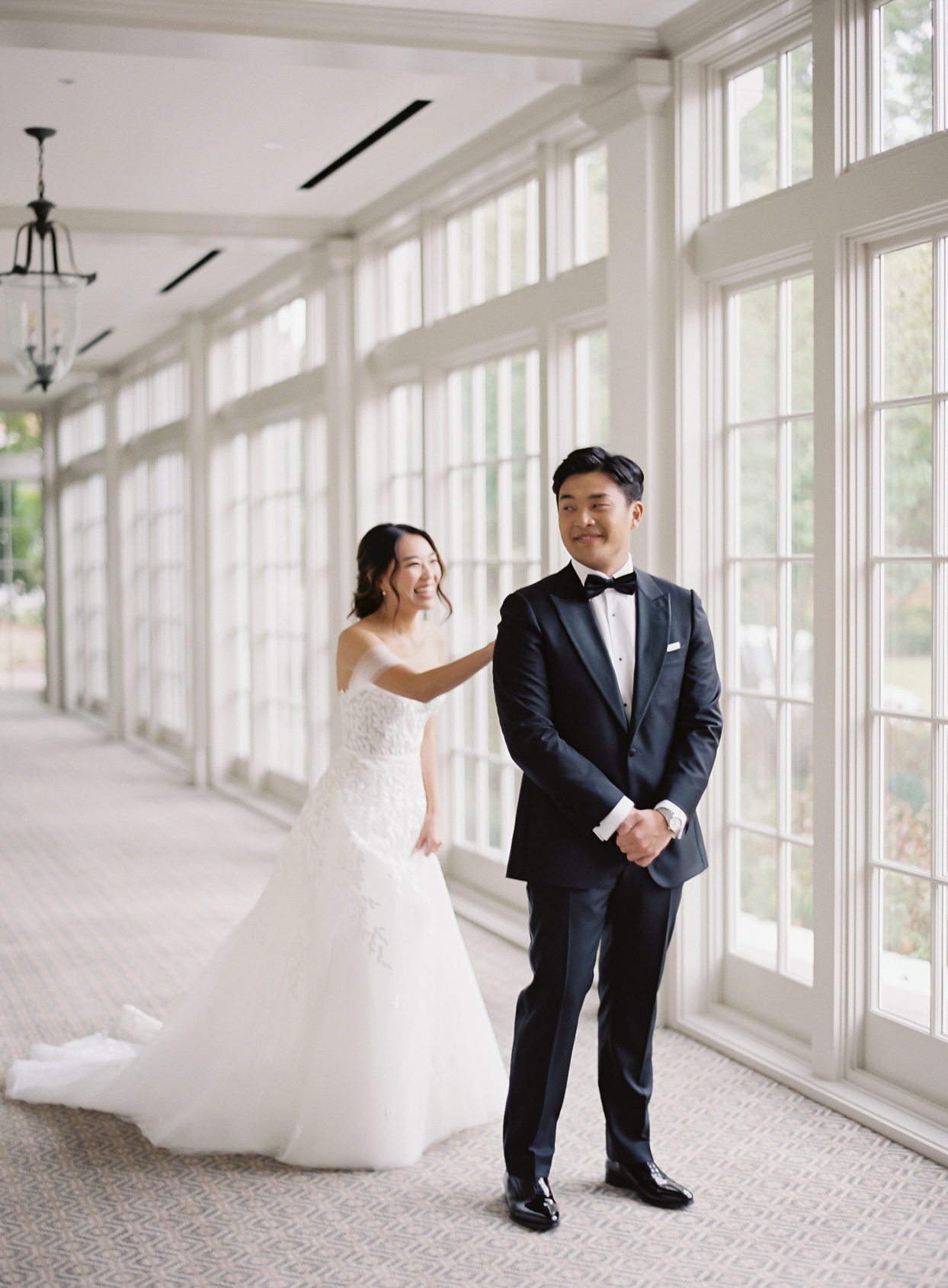 bride tapping groom's shoulder for first look in front of windows