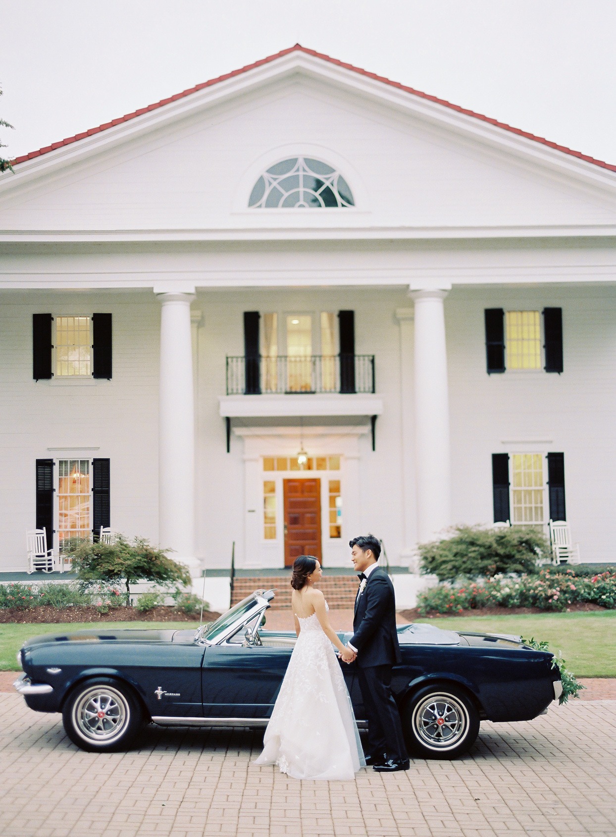 wedding couple holding hands in front of vintage mustang