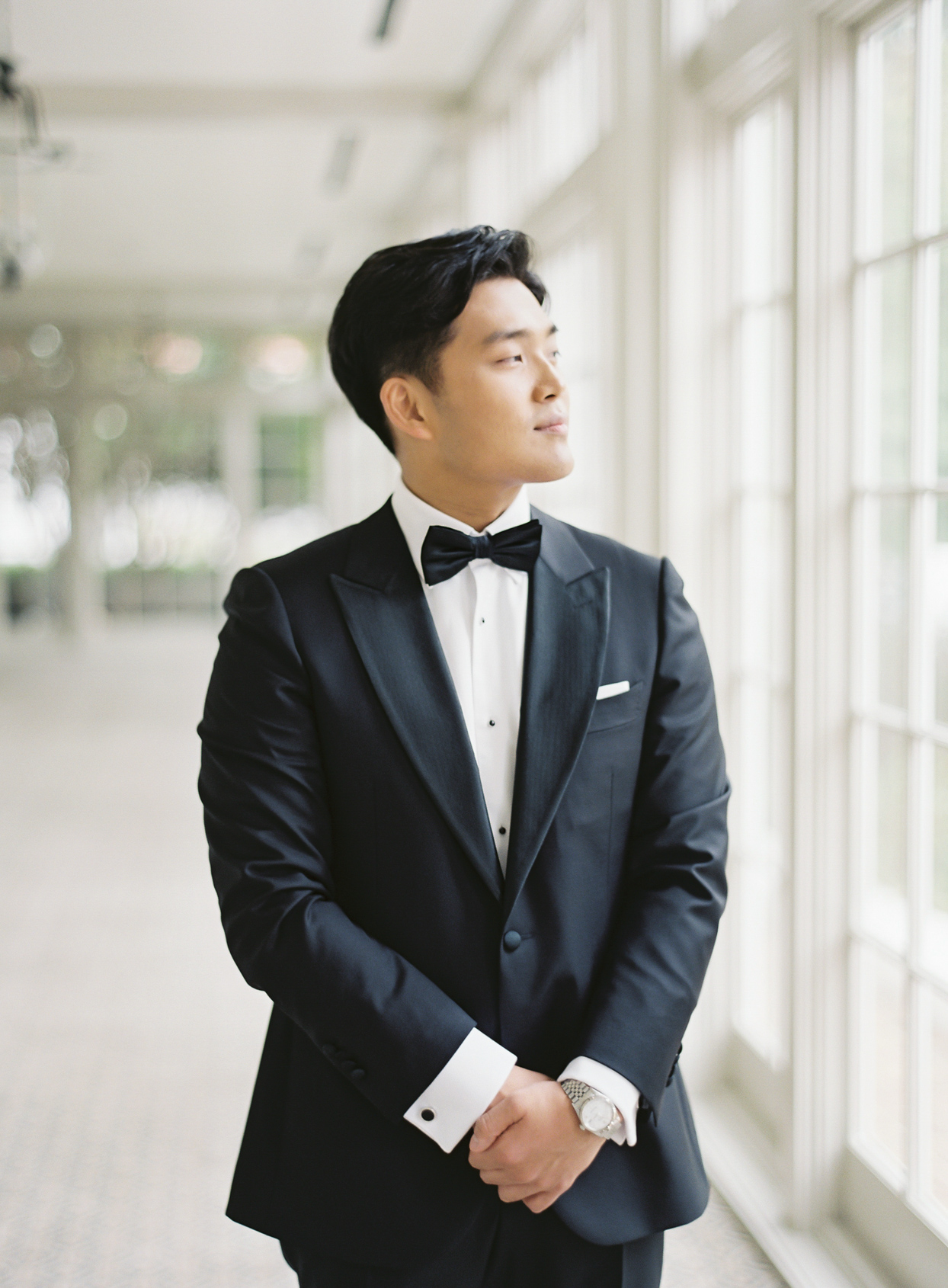 groom in black tuxedo with bow tie standing by windows