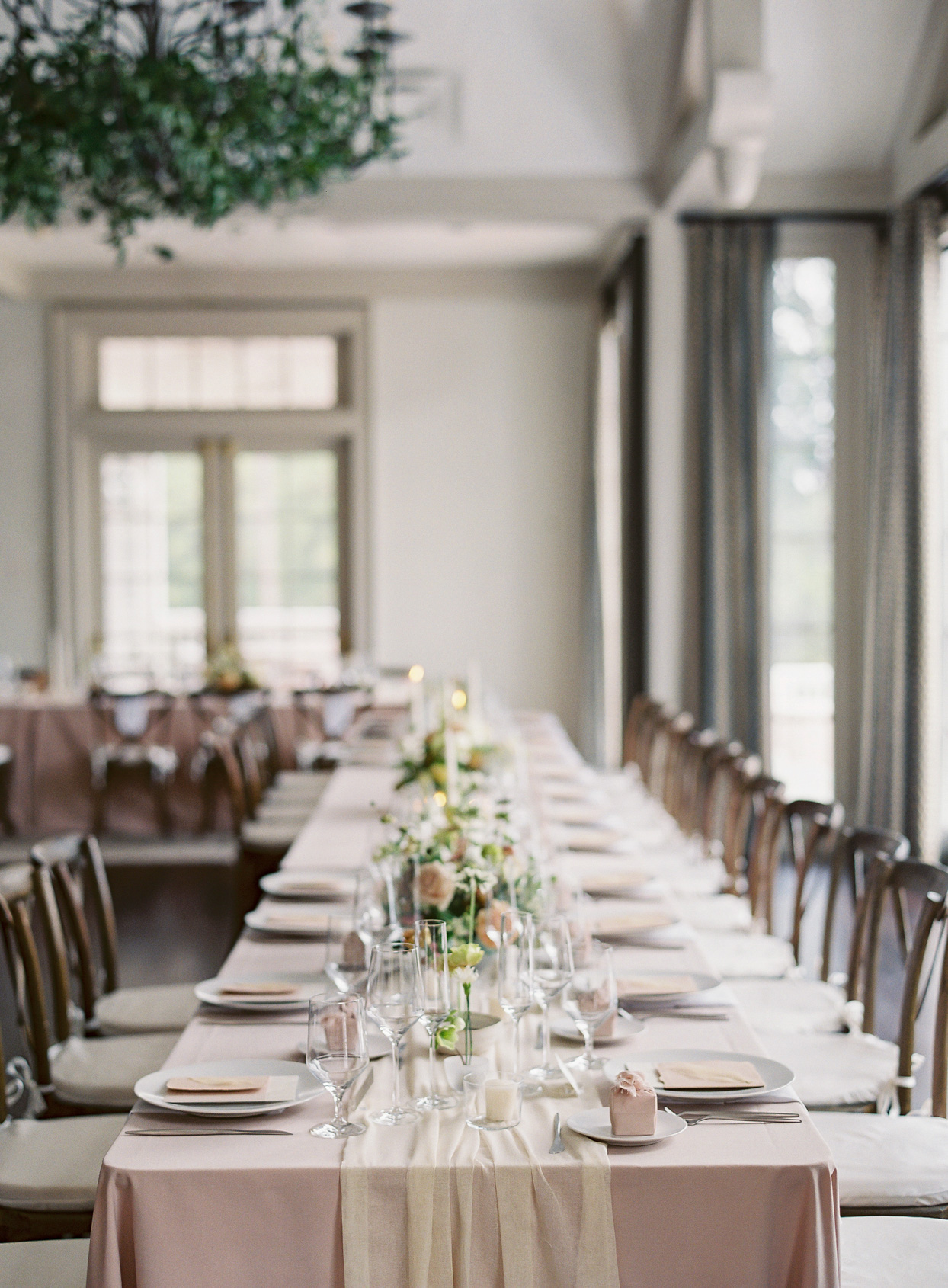 long tables with dusty rose table clothes and centerpieces
