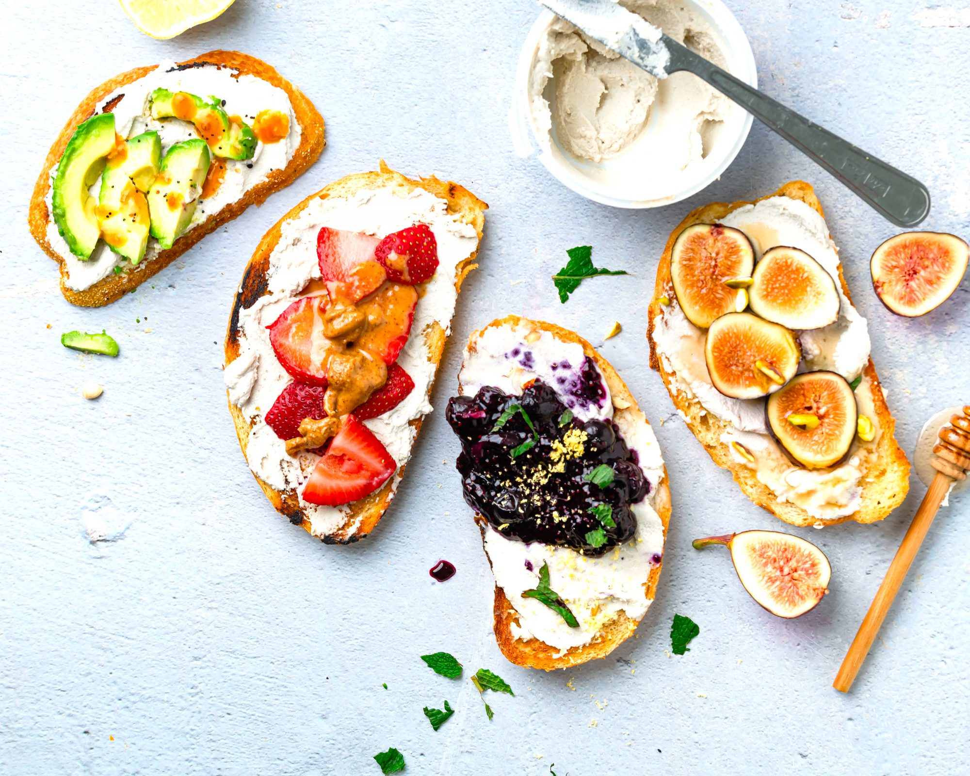 Toasts topped with vegan cream cheese and fruits, jam, and avocado