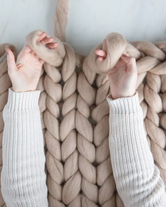 hands each creating a loop for arm knit blanket