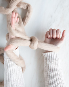 yarn looped around wrists for arm knit blanket