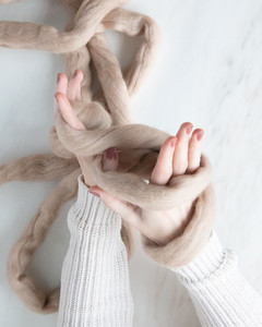 figure eight of yarn formed around hands and wrists for arm knit blanket