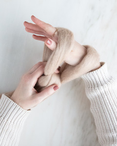 hand looping yarn around other hand for arm knit blanket