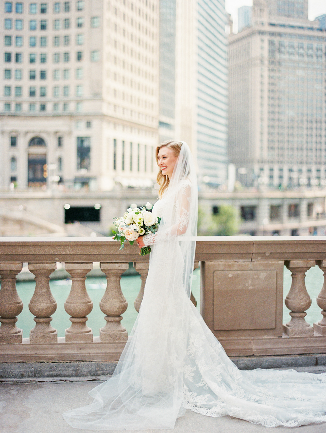 bride in white standing above chicago river