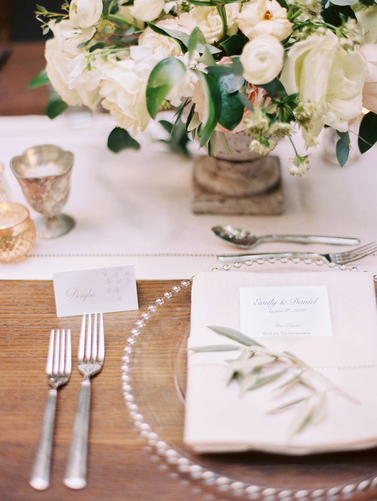 white place setting with clear charger and flowers