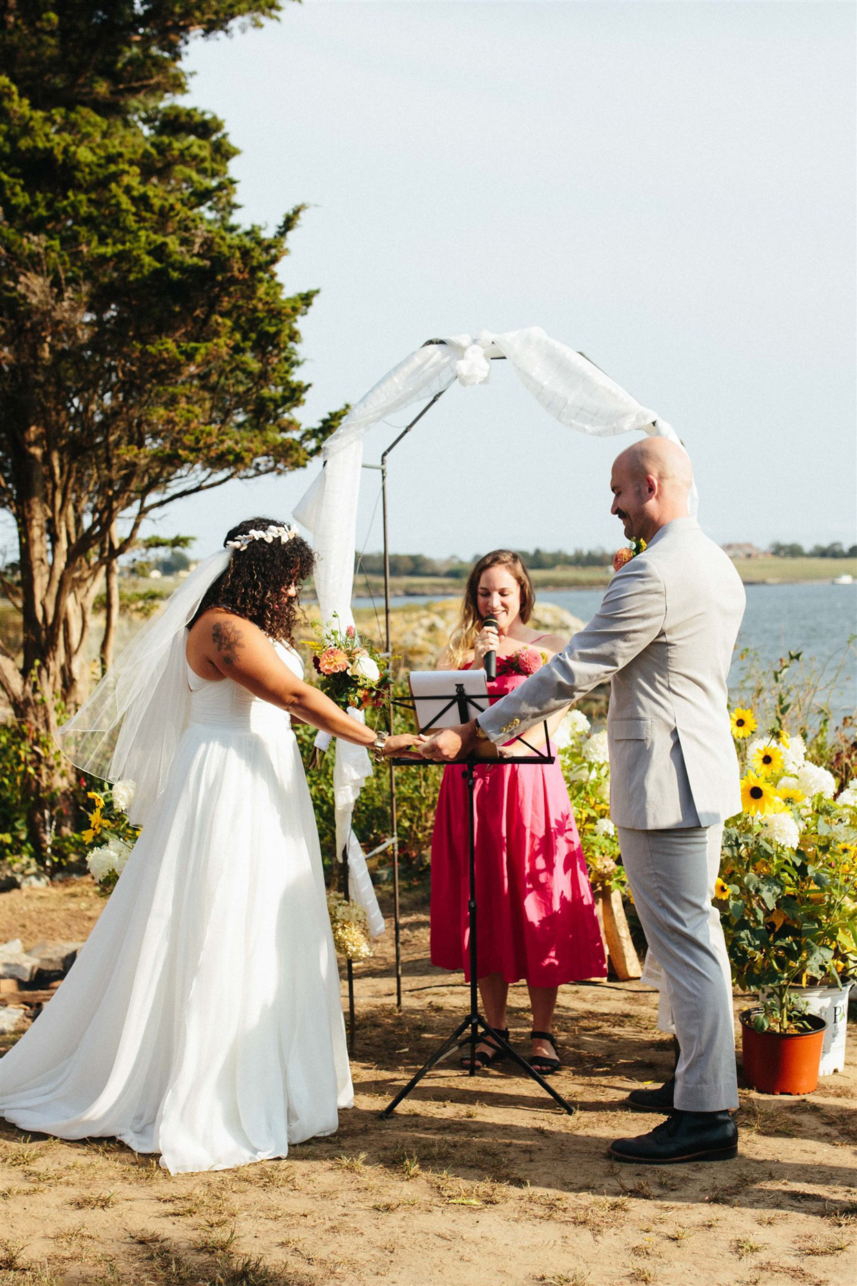 bride and groom holding hands for ceremony by the water