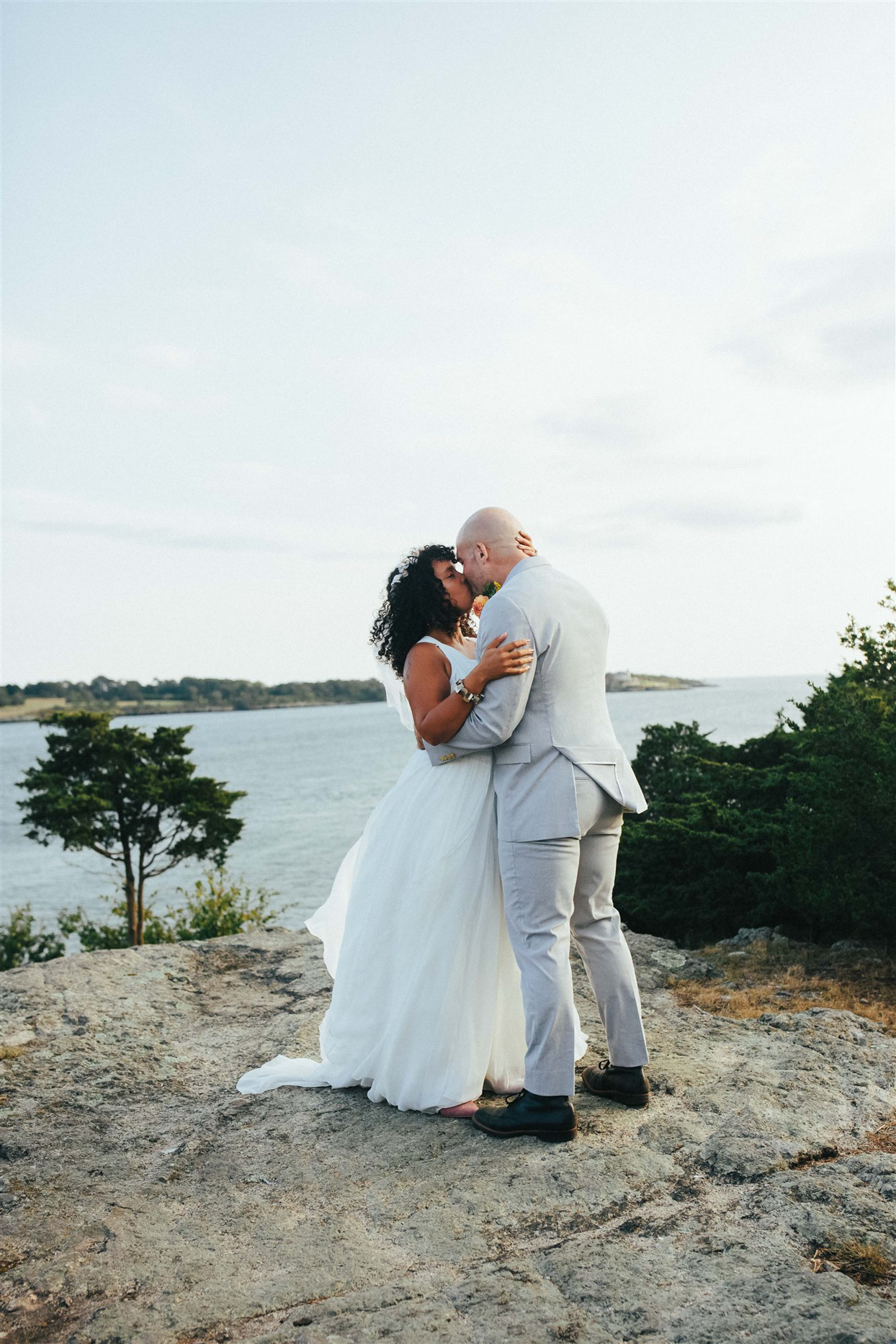 wedding couple kissing on rock overlooking water