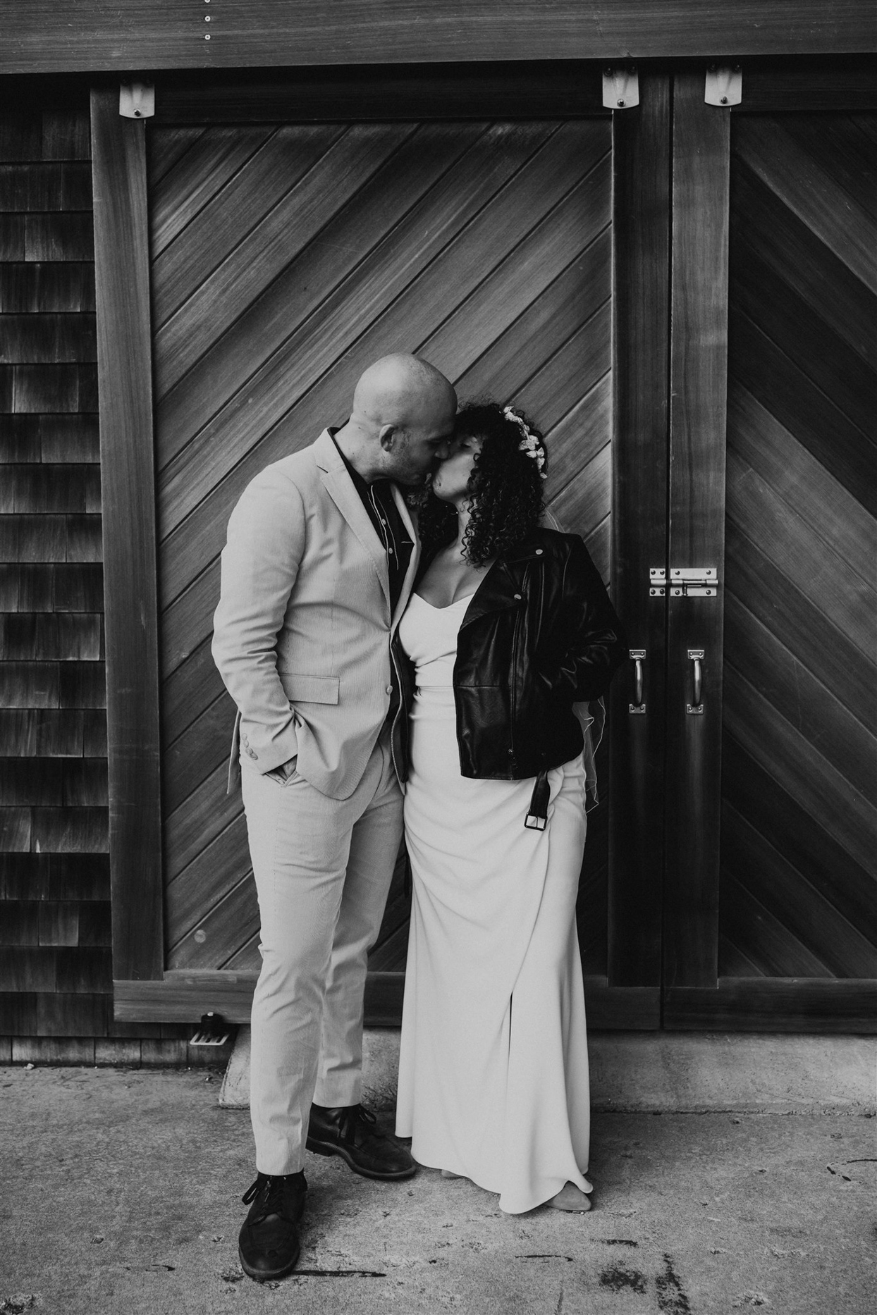 couple portrait kissing in front of wooden doors