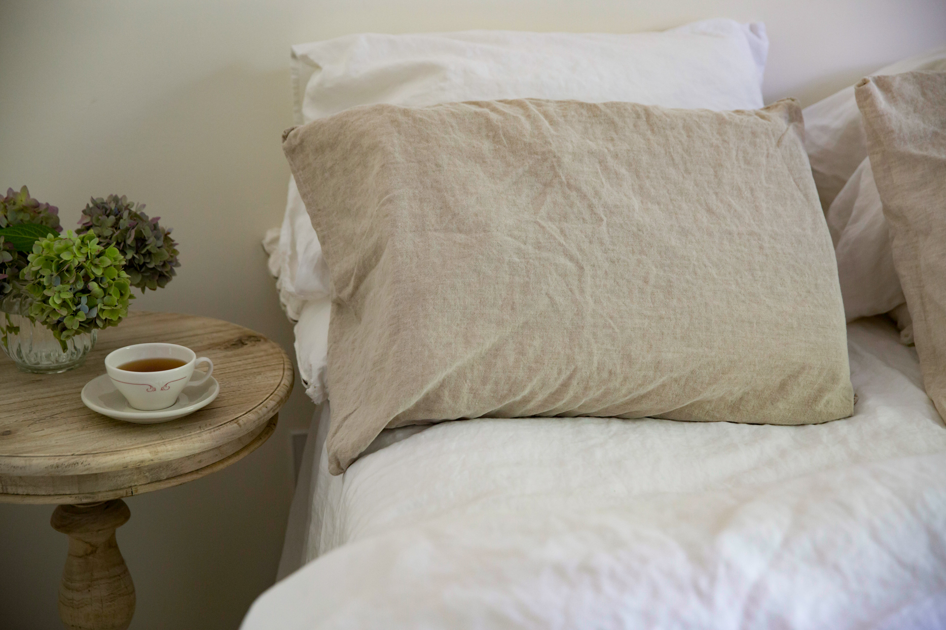 beige linen bedsheets and night table