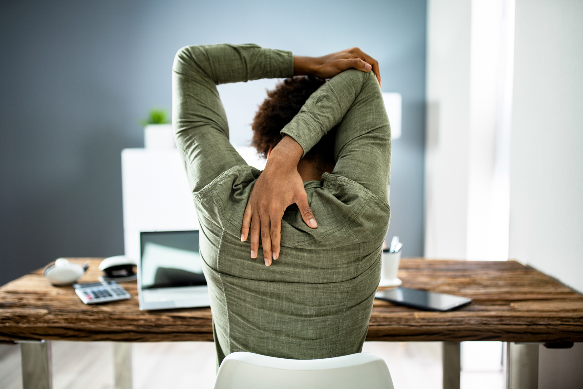 woman stretching at wooden desk