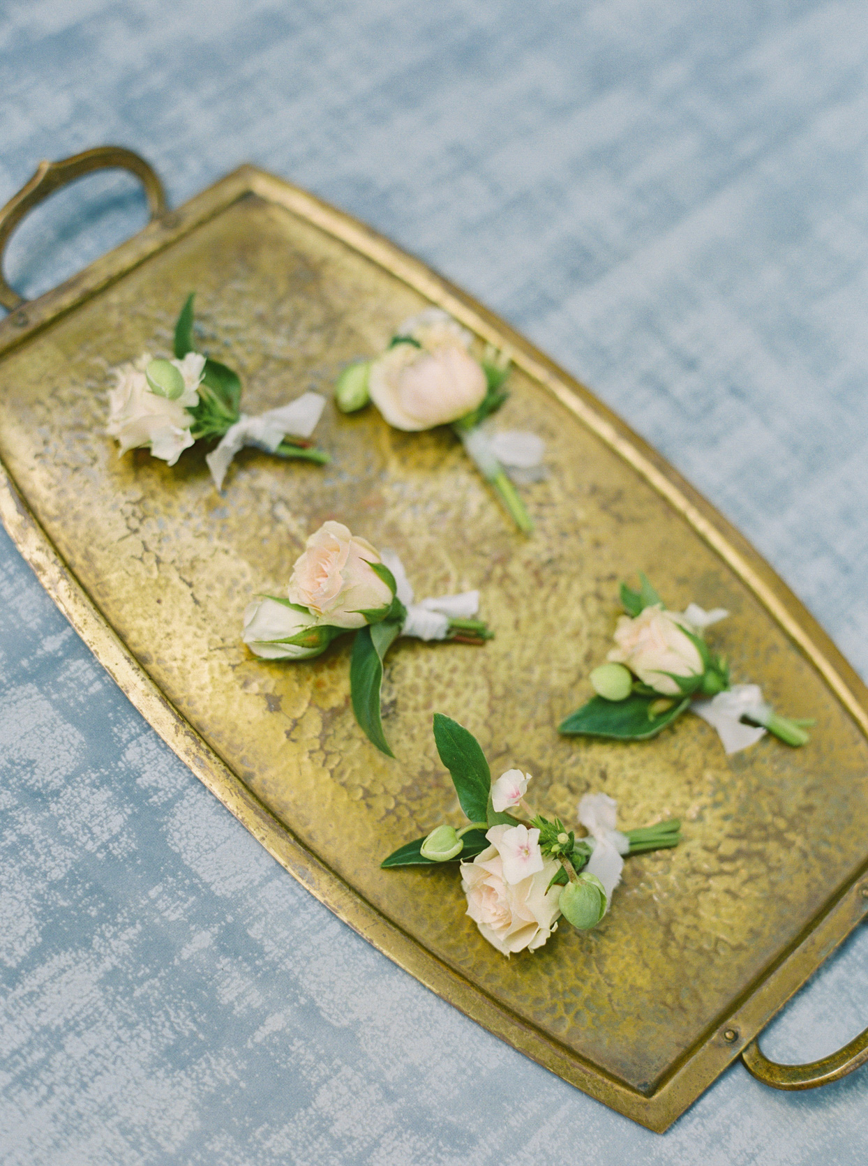 pale peach boutonnières on gold tray