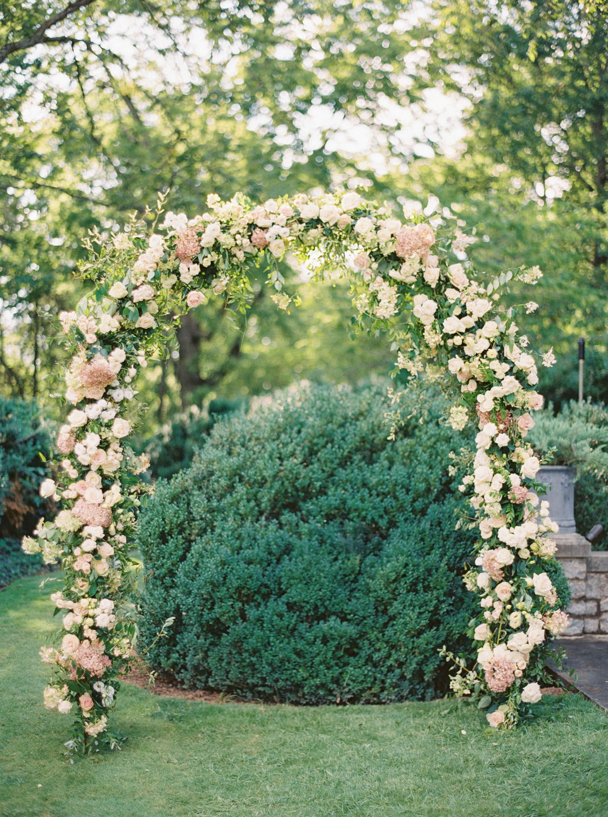 pink and peach floral arch in garden for wedding ceremony