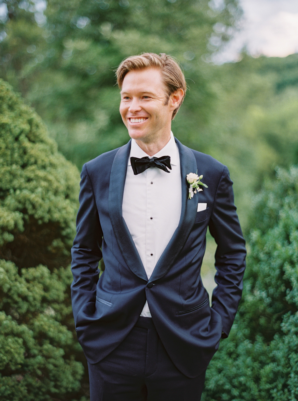groom in blue suit with bow tie