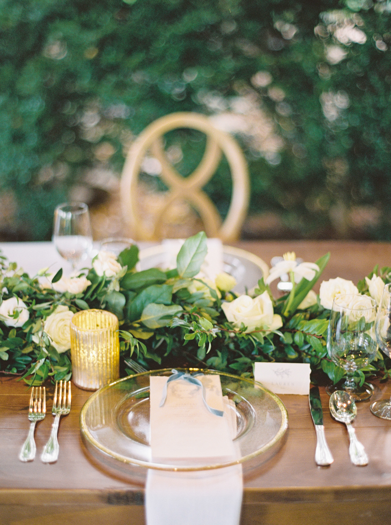 elegant wedding place setting on wooden table with greenery garland