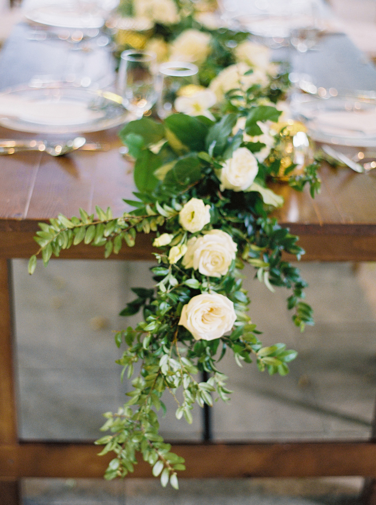 greenery garland with white flowers on wedding reception table