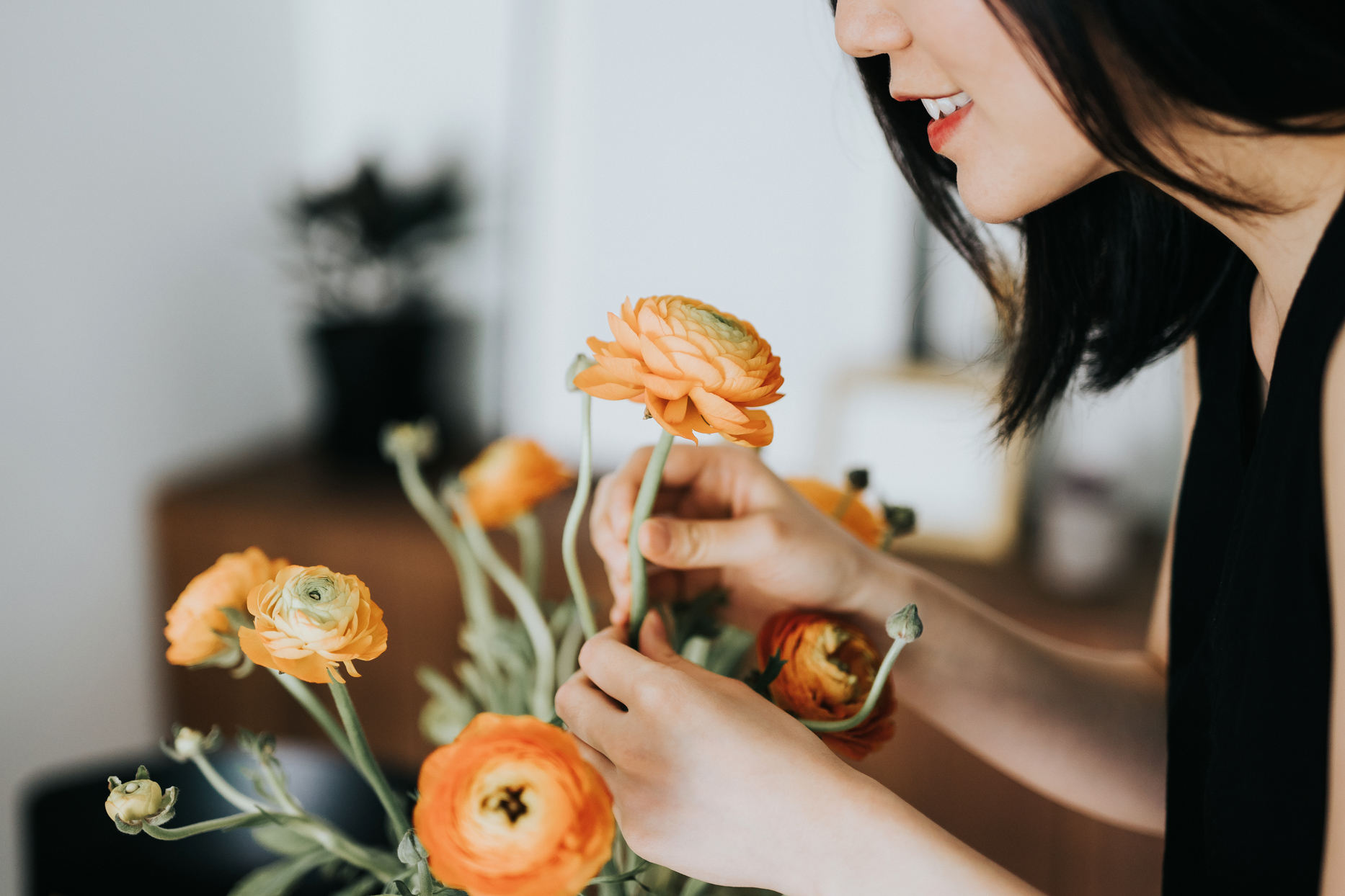 woman arranging orange ranunculus flowers