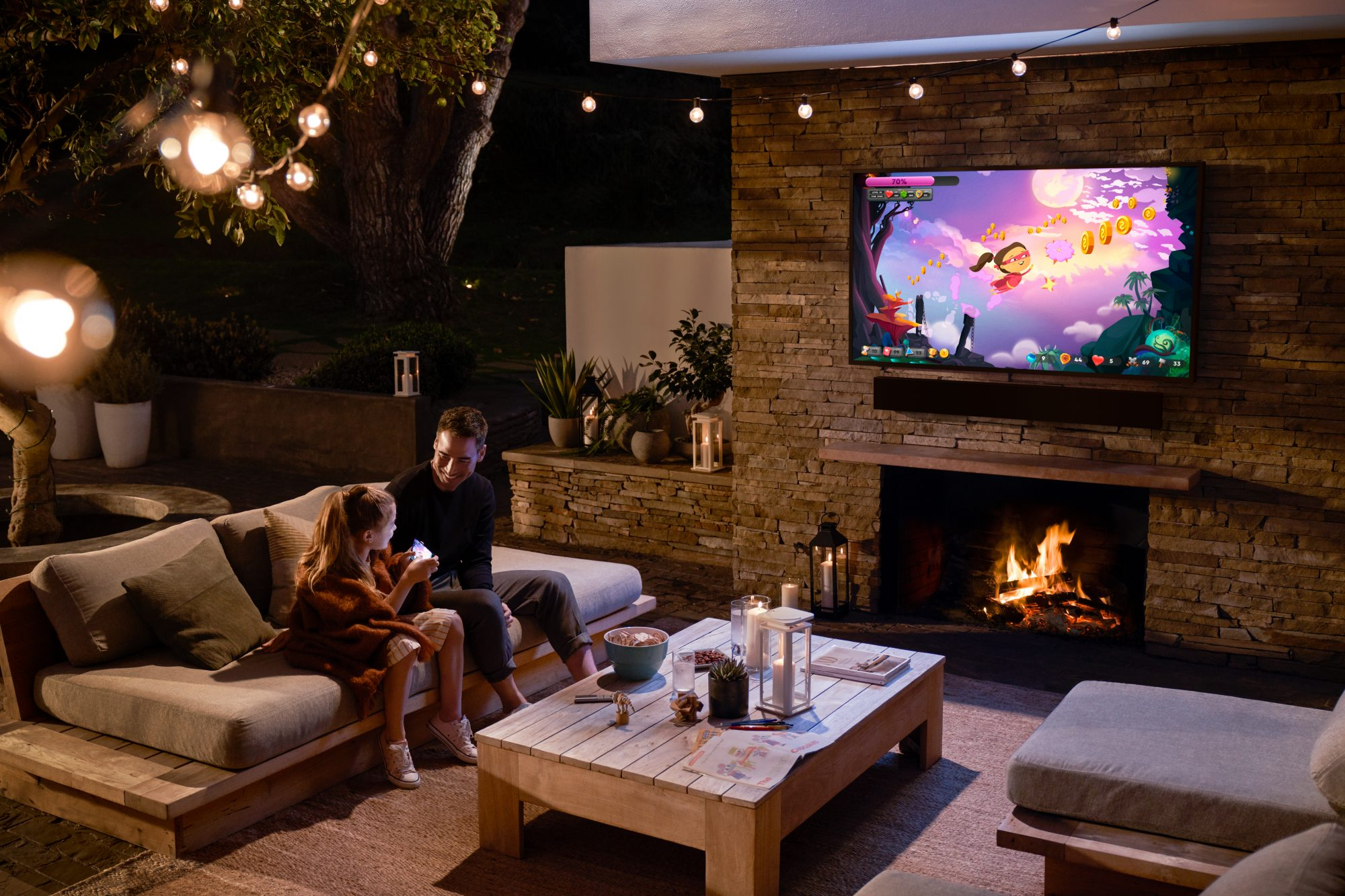 father and daughter smiling while watching tv outdoors