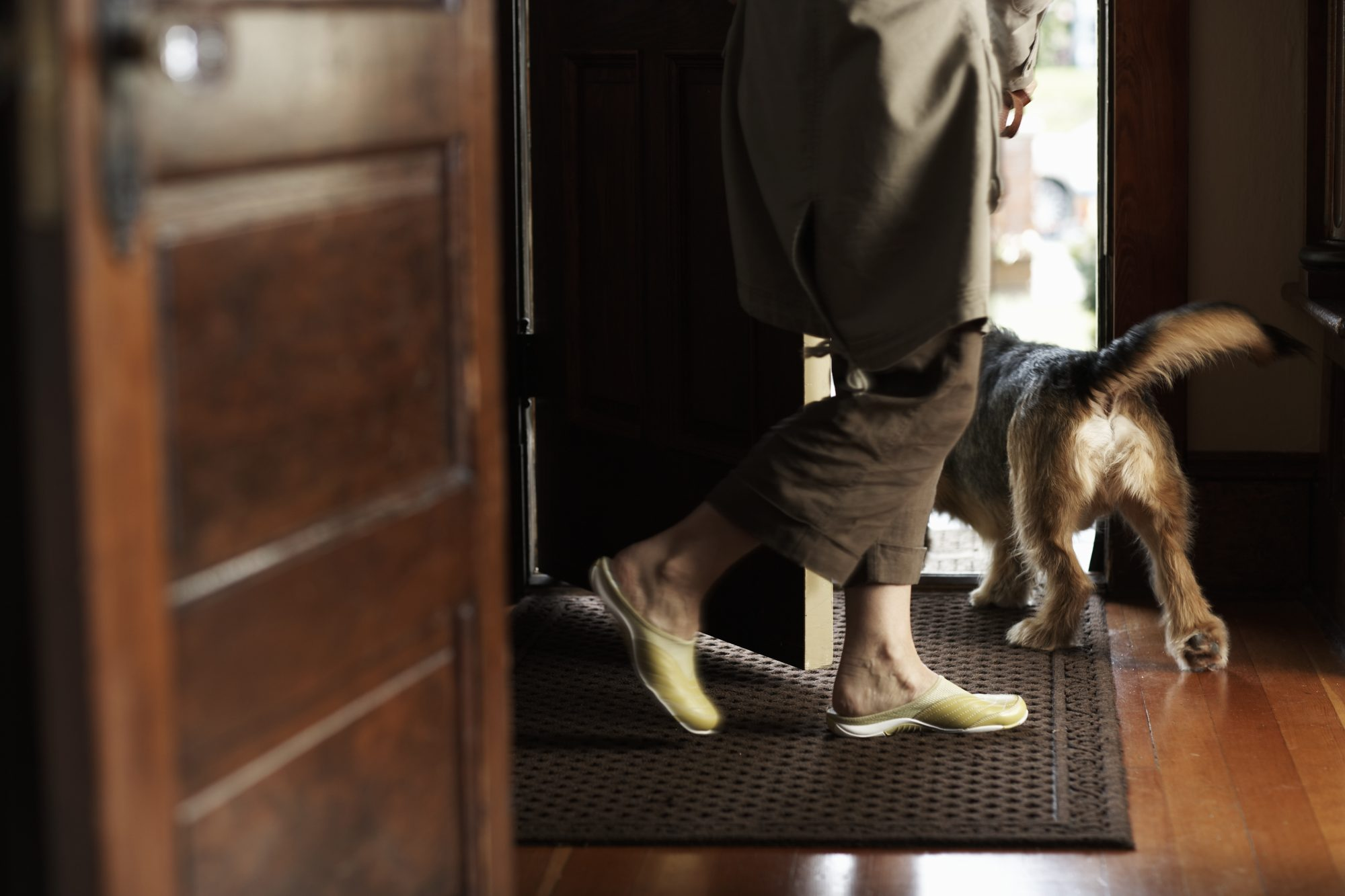 mature woman and dog walking on doormat and out of the front door