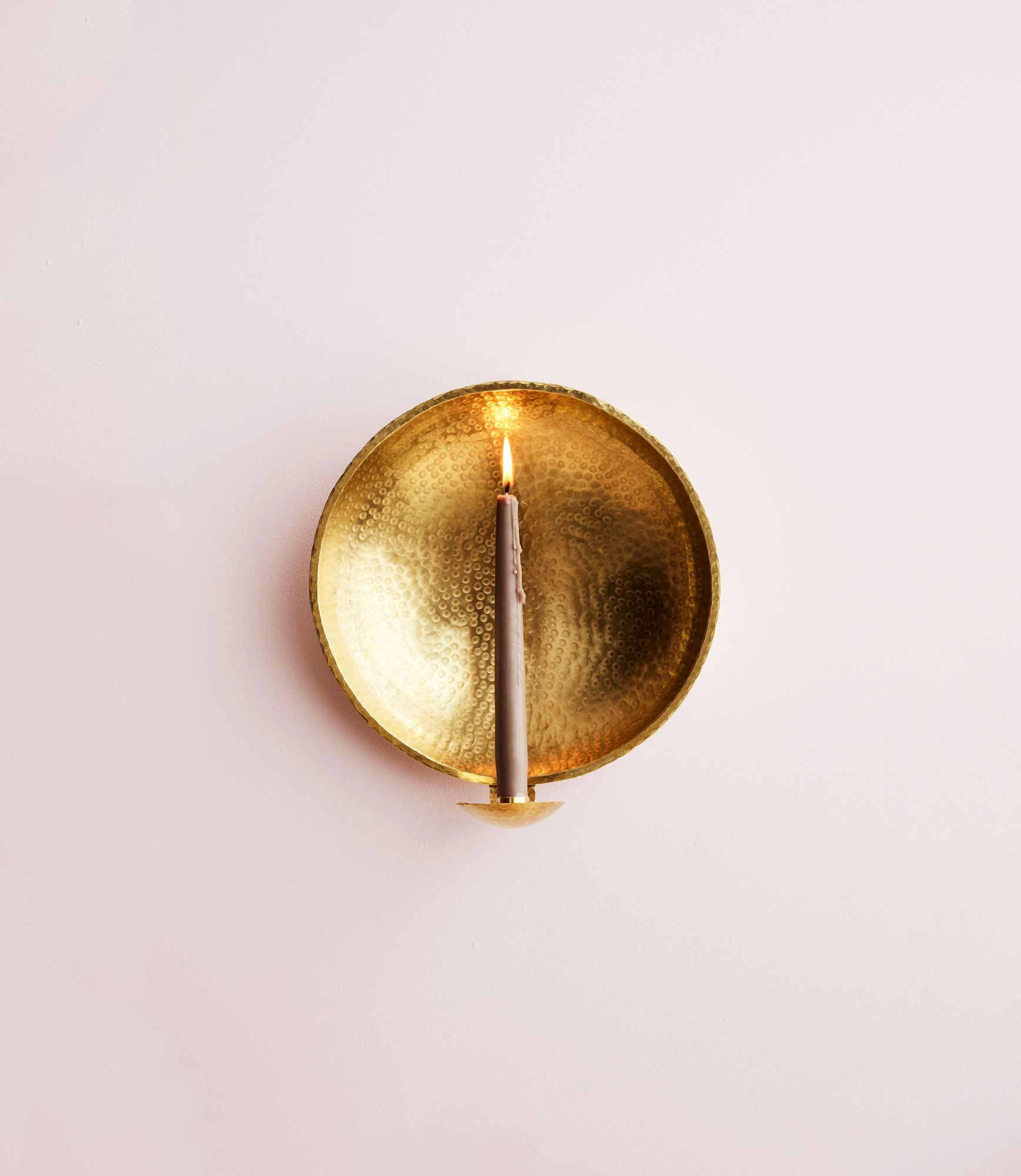 gold sconce with blush candle lit in the center against a blush wall