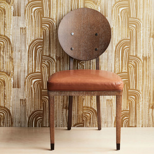 wood chair in front of gold graphic wallpapered wall