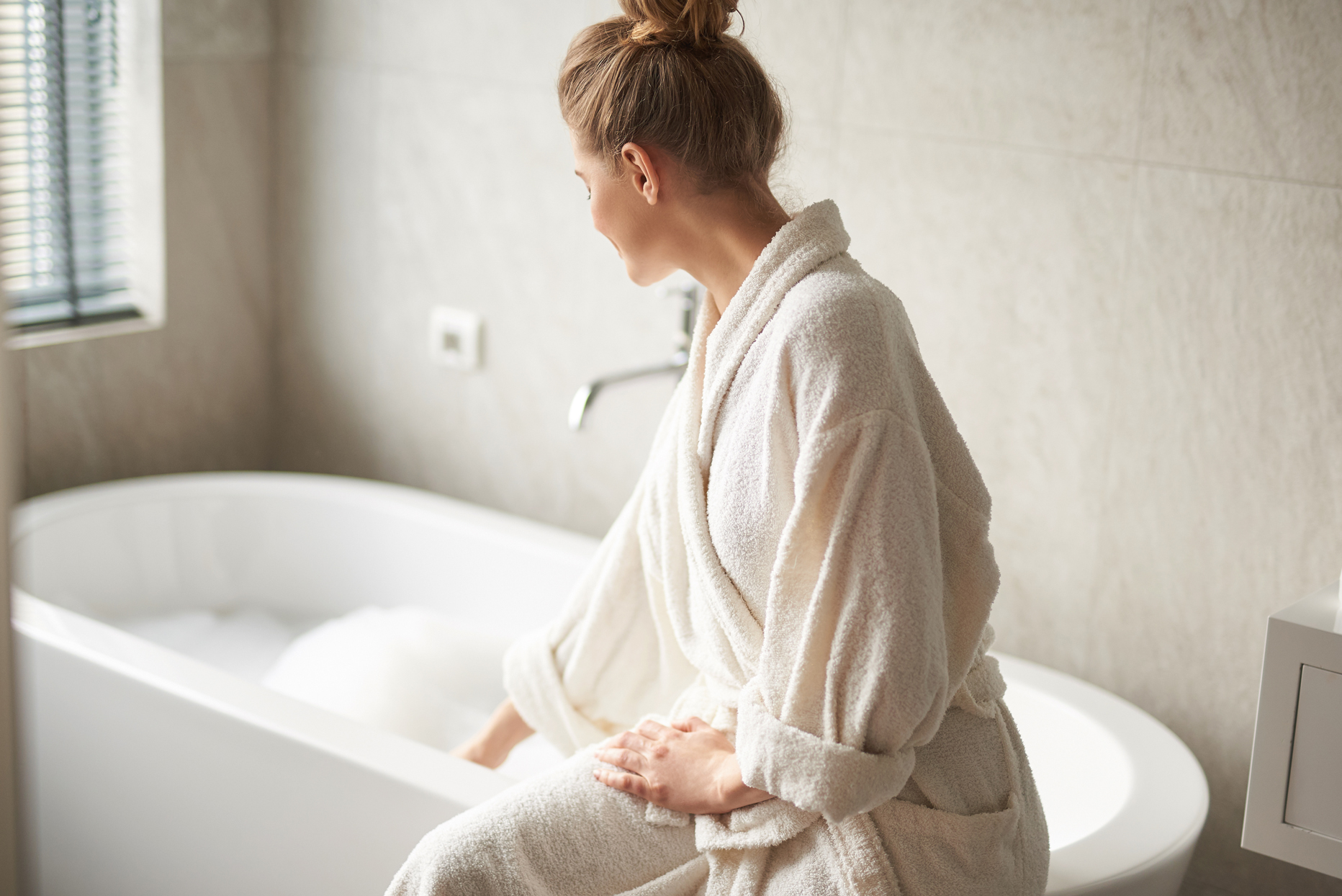 person wearing white bathrobe sitting on edge of tub filled with bubbles
