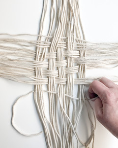 Begin weaving the cord in and out to form the base of the basket.