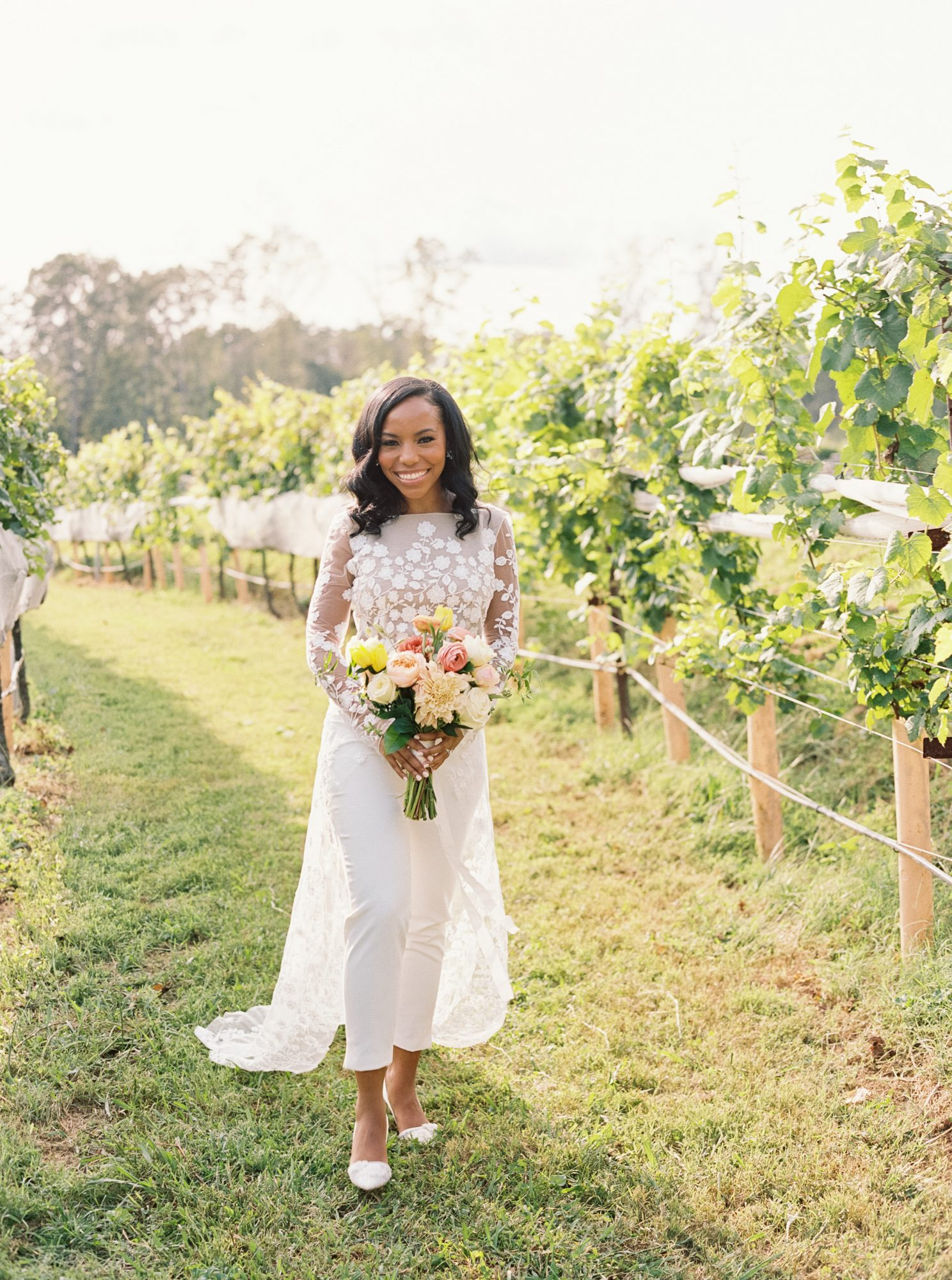 cayla david wedding bride wearing a white jumpsuit and holding a colorful bouquet at the outdoor winery venue