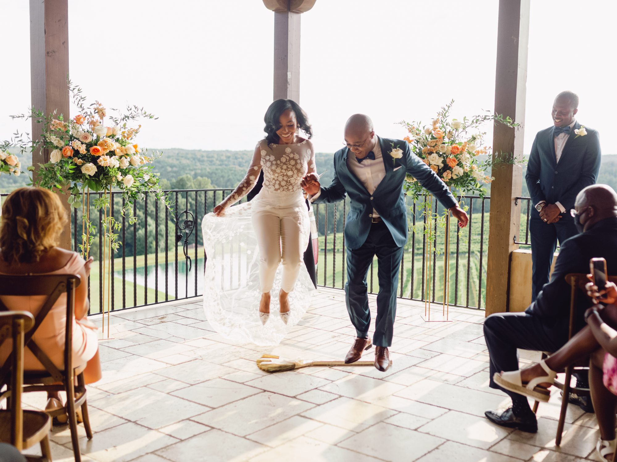 cayla david wedding couple holding hands and jumping the broom during ceremony
